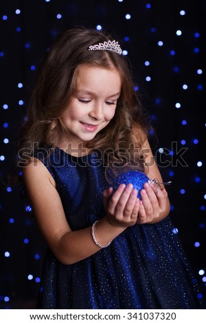 Happy pretty  child girl is holding blue Christmas tree ball in hands over background scene with lights, New years - stock photo