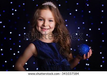 Happy pretty  child girl is holding blue Christmas tree ball in hands over background scene with lights, holiday concept - stock photo
