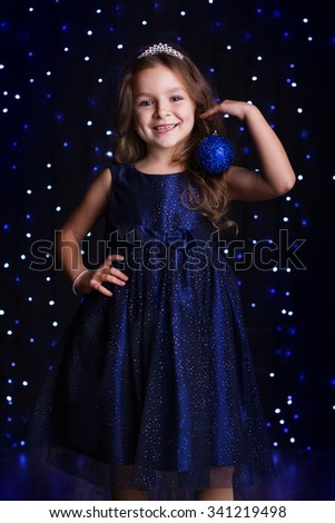 Happy pretty child girl is wearing fashion dress and holding blue Christmas tree ball in hands over background scene with lights, holiday concept - stock photo