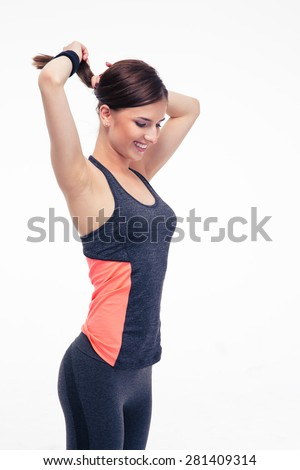 Happy pretty fitness woman holding her hair in ponytail isolated on a white background