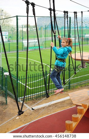 Happy pretty girl climbs on Rope way with safety rope on special playground - stock photo