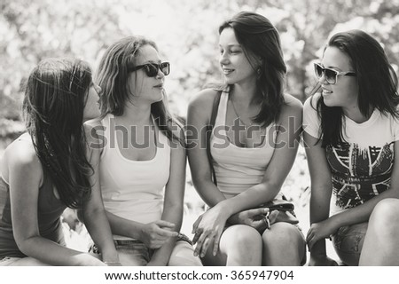 Happy pretty girl friends talking on summer green outdoors background, portrait