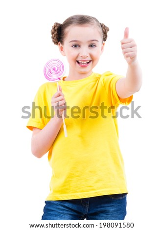 Happy pretty girl in yellow t-shirt with colored candy showing thumbs up sign - isolated on white. - stock photo