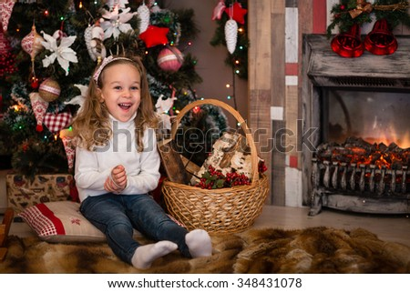 Happy pretty girl sits near Christmas tree in the room. Merry Christmas and New Year. - stock photo