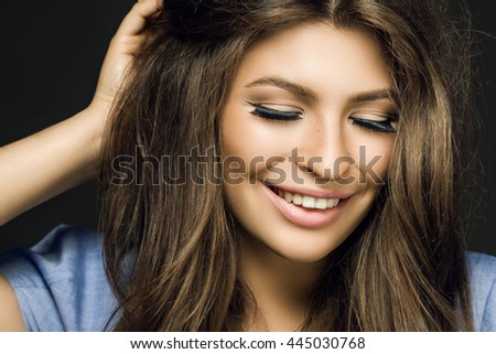 happy pretty girl smiling on a black background. a large portrait of a woman with long hair and make-up professionally. Lovely female smile with healthy white teeth