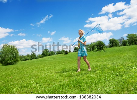 happy pretty girl with butterfly net standing on the green lawn