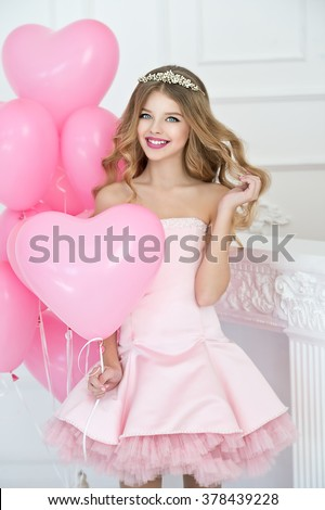 Happy pretty girl with pink balloons smiling and laughing at birthday party.  - stock photo