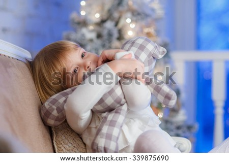 Happy pretty girl with toy bear sits on a sofa in the room. - stock photo