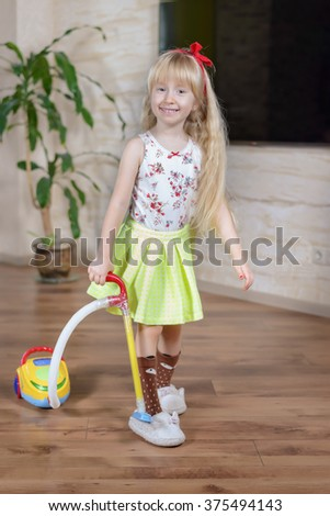 Happy pretty little blond girl with a lovely vivacious smile cleaning house with a colorful toy vacuum cleaner, full length portrait