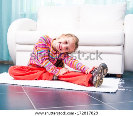 happy pretty little girl playing sports at home in front of a white sofa - stock photo