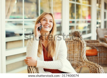 Happy pretty smiling woman talking on smartphone in cafe  - stock photo