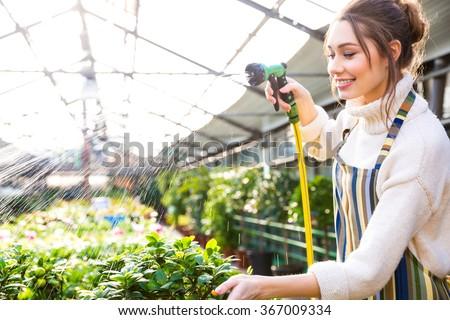 Happy pretty woman gardener in uniform watering plants with garden hose in greenhouse - stock photo
