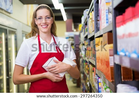 Happy pretty woman holding box at supermarket