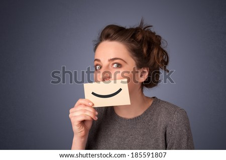 Happy pretty woman holding card with funny smiley on gradient background