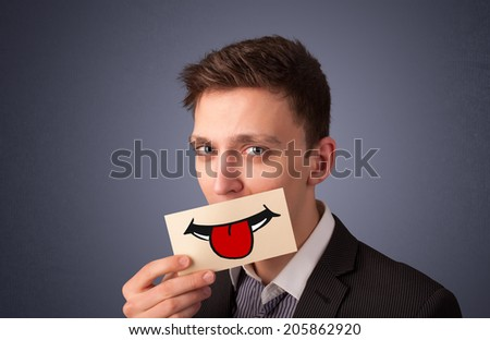 Happy pretty woman holding card with funny smiley on gradient background - stock photo