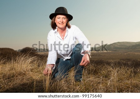 Happy pretty woman middle aged wearing a hat enjoying outdoors. Sitting in grassy dune landscape. Touching the grass. Feeling free. Clear sunny spring day with blue sky. - stock photo