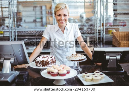 Happy pretty woman preparing plate of cake - stock photo