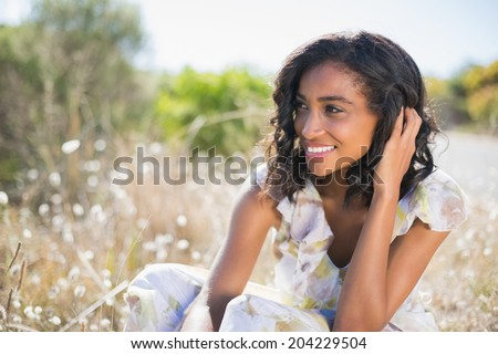 Happy pretty woman sitting on the grass in floral dress on a sunny day in the countryside - stock photo