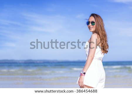 happy pretty woman smiling in the beach wearing a Black and white striped dress with the sea and horizon in the background - stock photo