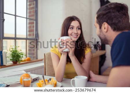Happy pretty young woman having morning coffee as she sits at the breakfast table with her husband smiling at him - stock photo