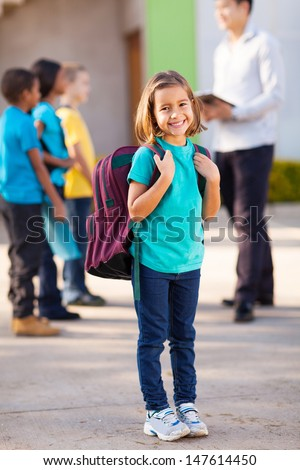 happy primary school student carrying backpack with classmates and teacher on background - stock photo