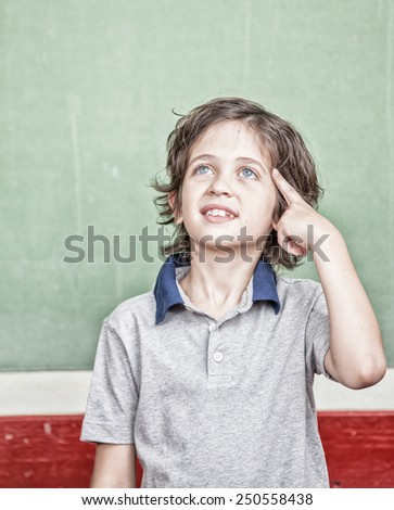 Happy primary school student thinking about the answer in front of chalkboard. - stock photo
