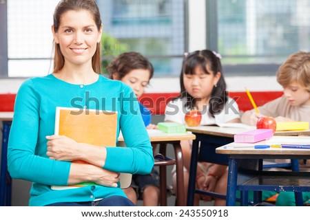 Happy primary school teacher smiling with students doing schoolwork. - stock photo