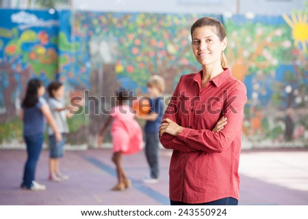 Happy primary school teacher with her students playing in schoolyard. - stock photo