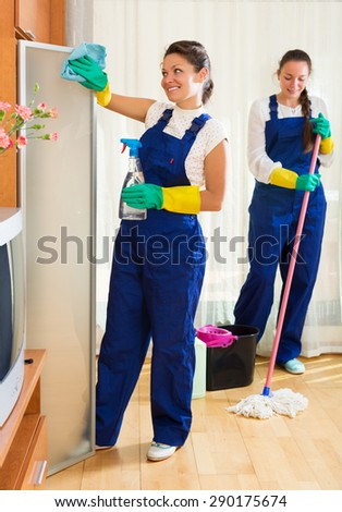 Happy professional cleaners washing apartment with rag and mop