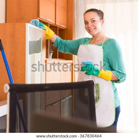 happy professional spanish cleaner  cleaning the office - stock photo