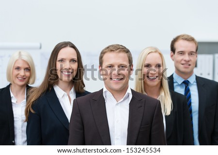 Happy professional young team made of three women and two men, all Caucasian, looking at camera and wearing formal suits and shirts - stock photo