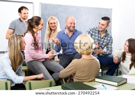 Happy professor chatting with his smiling graduates after a lecture - stock photo