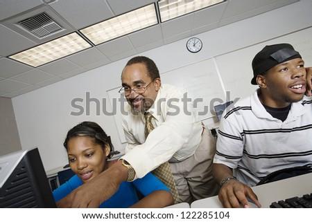 Happy professor teaching students in computer lab - stock photo