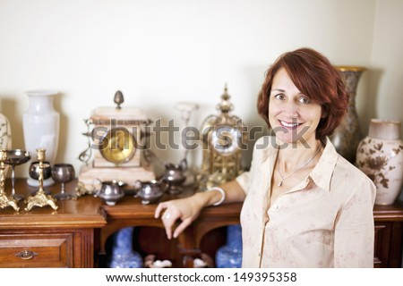 Happy proud woman standing next to her collection of antiques - stock photo