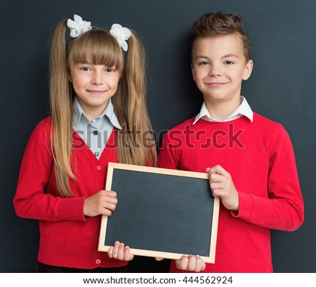 Happy pupil - teen boy and girl with small blackboard in front of a big chalkboard. Back to school concept. - stock photo