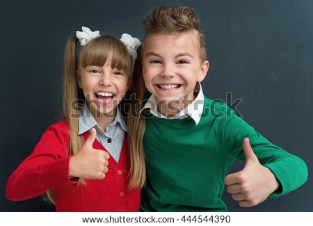 Happy pupils - boy and girl, showing thumbs up gesture in front of a big chalkboard. Back to school concept.  - stock photo