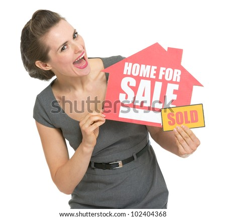 Happy real estate owner with home for sale sold sign