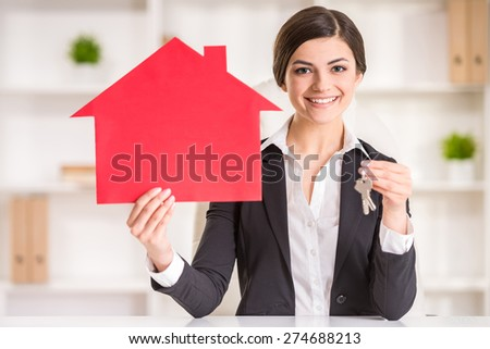 Happy realtor woman is showing home for sale sign and keys.