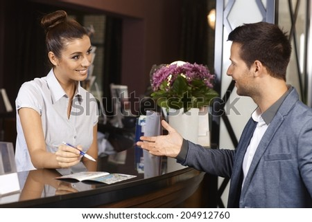 Happy receptionist and guest talking at hotel reception. - stock photo