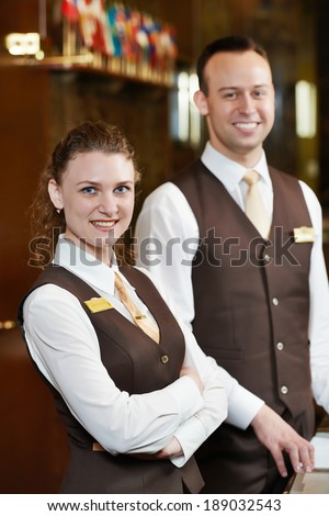 Happy receptionist workers standing at hotel counter