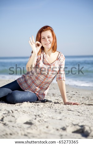 Happy red-haired girl at the beach. Outdoor shot.