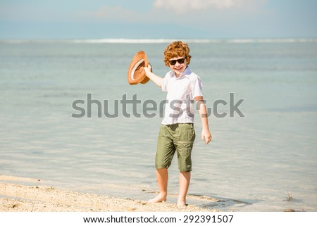 Happy red haired kid boy wearing hipster sunglasses waving hat enjoying beautiful summer sunny day stays on the beach in shallow water. Happiness, travel, vacation concept