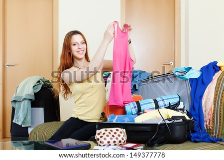 happy red-haired woman with luggage in home going on holiday