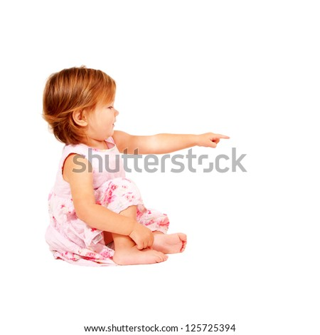 """Happy redhead baby pointing at something or clicking on something. Kid asking """"what is it?"""" A side view. Ready for your logo or text. Isolated on white background - stock photo"""