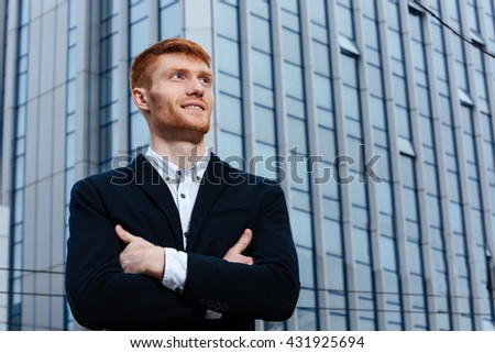 Happy redhead businessman with arms folded standing with glass building on backgorund