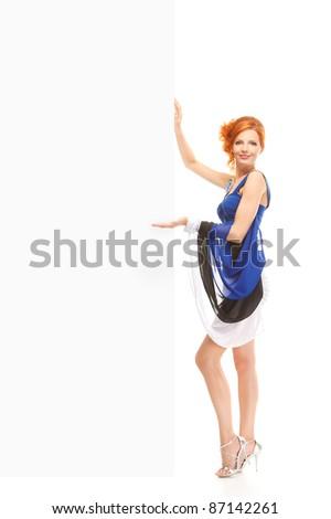 happy redhead girl wearing estonian flag dress showing blank billboard over white background - stock photo