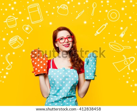 Happy redhead housewife with oven gloves on yellow background - stock photo