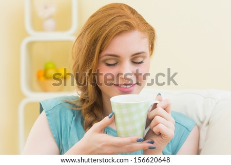 Happy redhead sitting on the couch smelling coffee at home in the living room