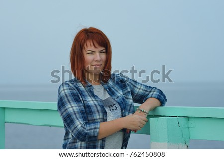happy redhead woman standing near the sea
