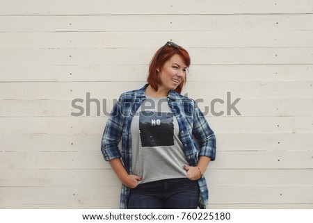 happy redhead woman standing near the wall